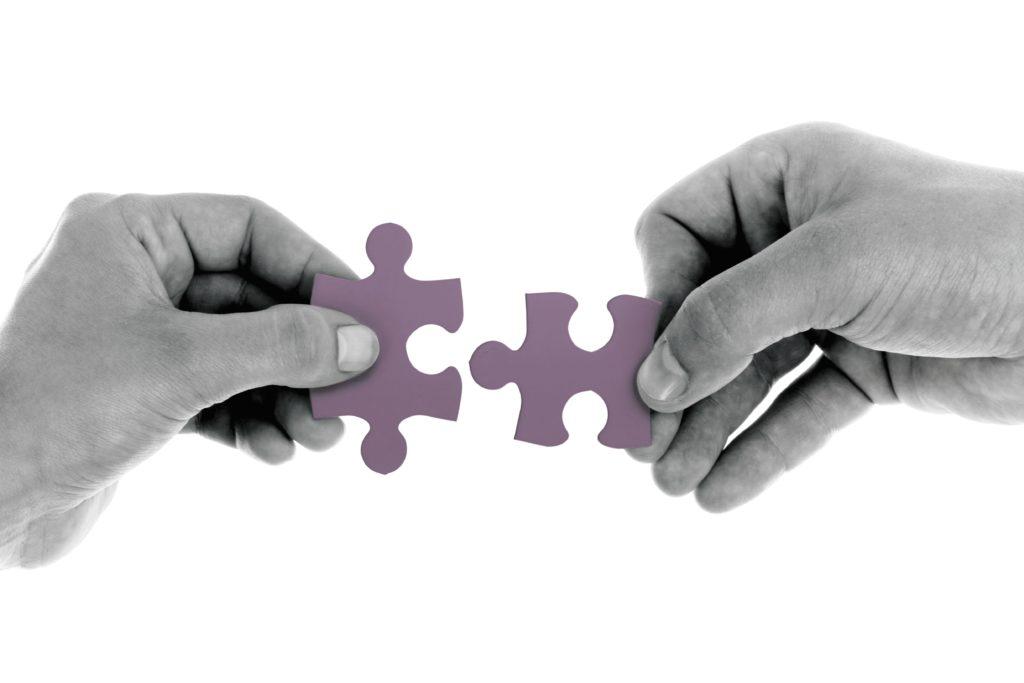 Zwei Hände mit Puzzlestücken